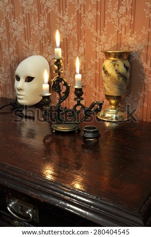 Elegant still life with  bronze candelabra, antique goblet and a mask on an old  wallpaper background - stock photo
