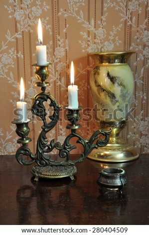 Elegant still life with ornate bronze candelabra and antique goblet on an old wallpaper background