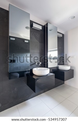 Elegant Stone Bathroom With Two Sinks And Large Mirrors Hunging On The Gray  Wall
