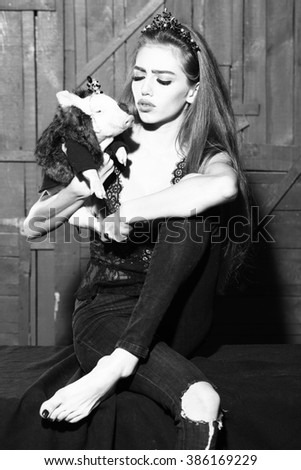 Elegant stylish young woman in thin rim holding cute little pig in hands in fur coat indoor on wooden background black and white, vertical picture