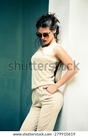 elegant summer fashion young woman wearing  golden overalls, hair in bun and sunglasses, shot in the city - stock photo