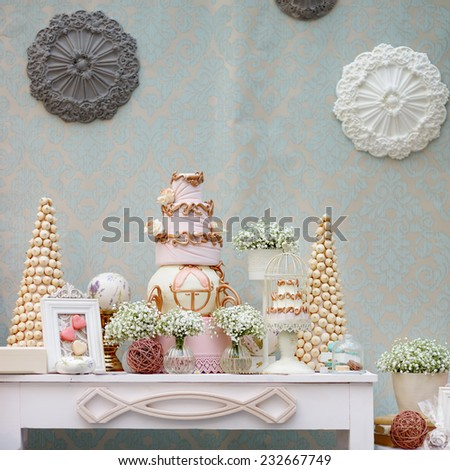 Elegant sweet table with big cake and macaroon on dinner or event party  - stock photo