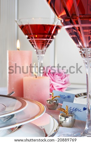 """Elegant table ready for Valentine dinner, with crystal wine glasses and little """"me"""" and """"you"""" cards - stock photo"""