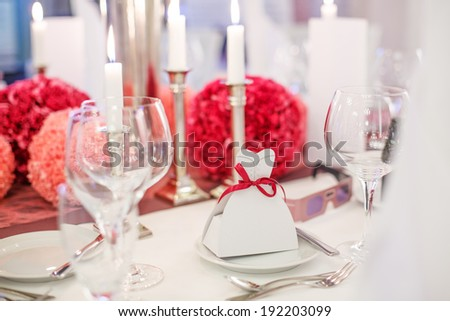 Elegant table set  for wedding or event party in soft red and pink, with paper bride and groom - stock photo