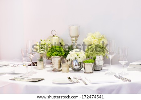 Elegant table set in green and white for wedding or event party - stock photo