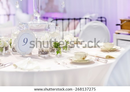 Elegant table set in green and white for wedding or event party, indoor. Flower arrangements, china and porcelain tableware and napkins. Wedding details. - stock photo