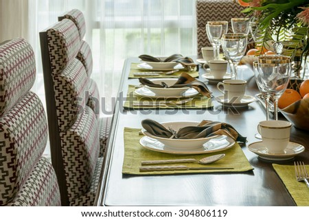 elegant table set in modern style dining room interior - stock photo