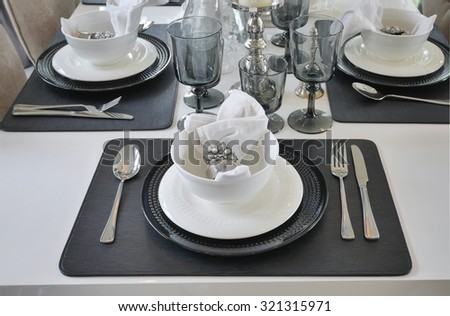 elegant table set on dining table in modern style dining room interior - stock photo