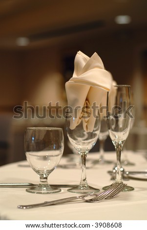 Elegant table setting at a wedding; focus on the napkin in the wine glass - stock photo