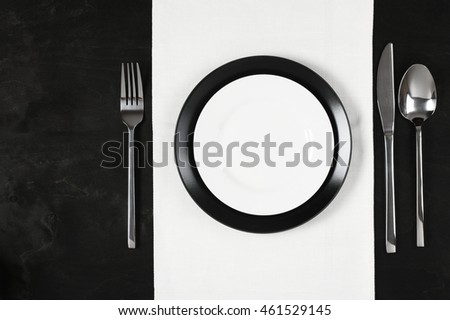 Elegant table setting: black and white plates with white linen and silverware on black wooden table. Top view point.