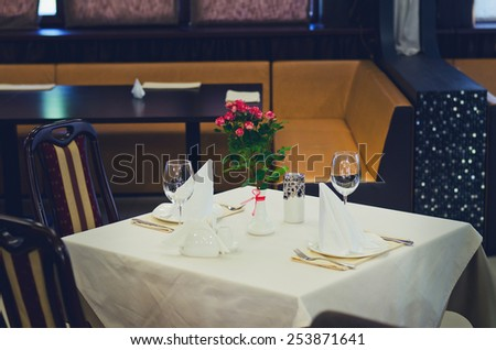 Elegant Table Setting, with Fresh Flowers on Vase at the Center, in Expensive Restaurant