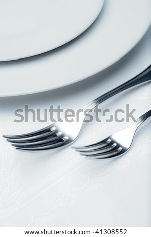 elegant table setting with silverware and plate-closeup of forks - stock photo