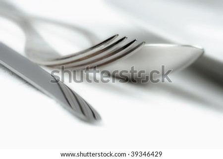 elegant table setting with silverware on white cloth - stock photo