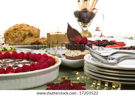 Elegant table with many desserts and fruits (eclair, pecan swirl cake, raspberry pie, cheese cake, creme caramel, and more)