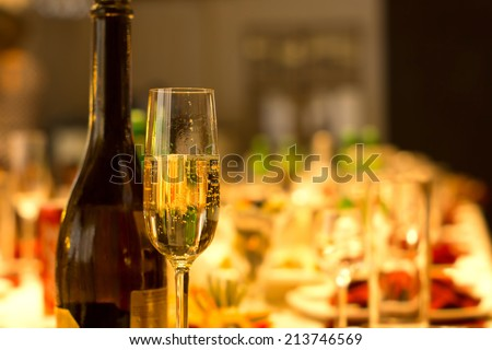 Elegant tall flute of chilled sparkling champagne standing alongside a full bottle on an elegant formal dining table at a catered event, party or reception - stock photo