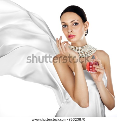 Elegant tanned woman with perfume and pearl jewellry - stock photo
