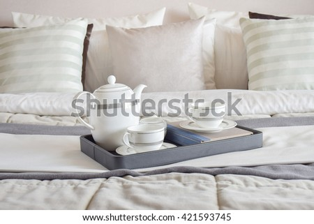 elegant tea cup set on black tray and books in modern bedroom interior - stock photo