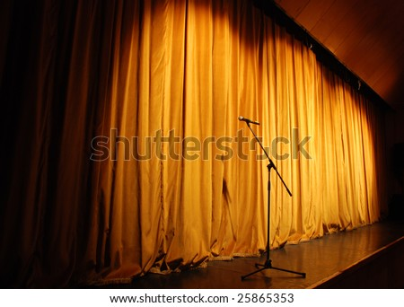elegant theater stage, orange curtain with microphone - stock photo