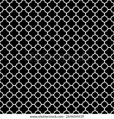 Elegant traditional cloverleaf quatrefoil pattern in monochrome black & white.  It has a seamless repeating white quatrefoil pattern on a black background.  - stock photo