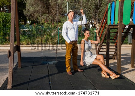 Elegant trendy young couple in fashionable modern clothes and accessories posing outdoors in the summer sunshine in a garden or park