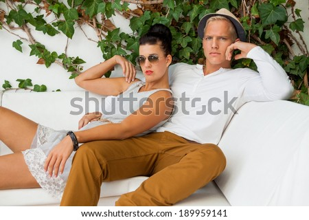 Elegant trendy young couple in fashionable modern clothes and accessories posing outdoors in the summer sunshine in a garden or park - stock photo