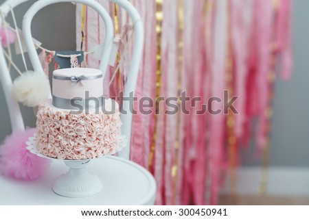 Elegant two-tier birthday or wedding cake with ruffled fondant bottom. Hand decorated artisanal cake. Tilt-shift effect. - stock photo