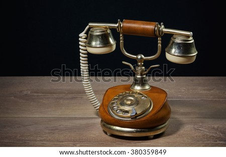 Elegant vintage phone on a wooden table with black background - stock photo