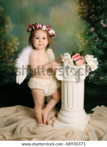 Elegant vintage style portrait of a baby girl dressed with angel wings and a flower halo headband - stock photo
