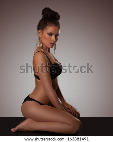 Elegant voluptuous woman in lingerie with gold earring and a neat bun kneeling on the floor looking seductively at the camera - stock photo
