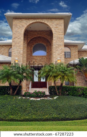Elegant waterfront home in tropical Florida . Entryway stands over two stories tall, with luxurious landscaping around the enormous arcade style archway. Circle drive leads around double door entry.