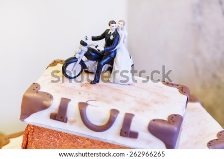 Elegant wedding cake in white with three levels. Icing with cream, marzipan, details of cake. With bride and groom figures. - stock photo