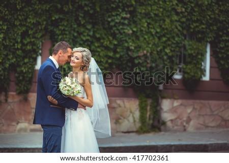 Elegant wedding couple near old vintage house - stock photo