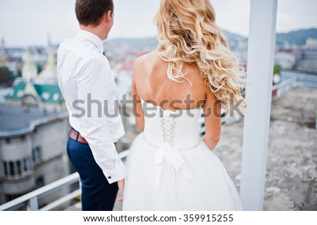 Elegant wedding couple on the roof with high-tech architecture line - stock photo