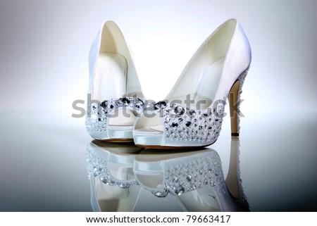 Elegant wedding shoes over gradient gray background - stock photo