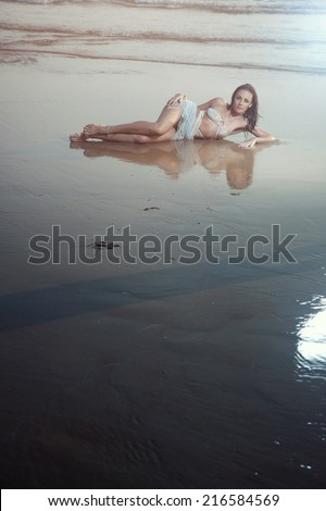 Elegant wet woman laying at the summer beach