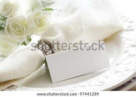 Elegant white Wedding place setting with beautiful white roses and a blank card