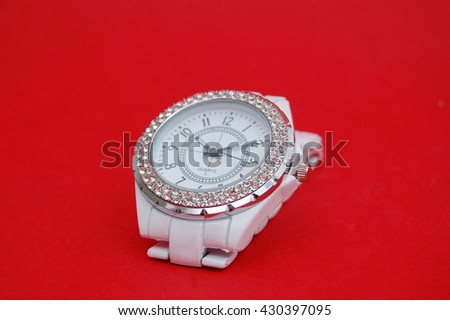 Elegant white wrist watch on red background - stock photo