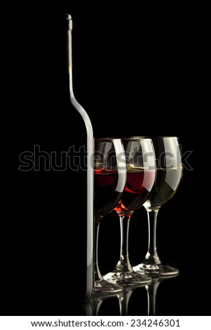 Elegant wine bottle with red, white and rose wine glasses in a black background  - stock photo