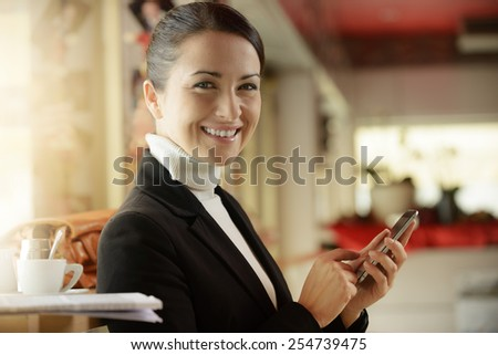 Elegant woman at the bar texting with her touch screen mobile phone - stock photo