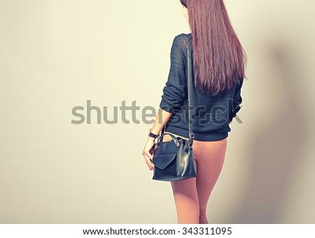 Elegant woman  black hand bag, rear view, studio image - stock photo