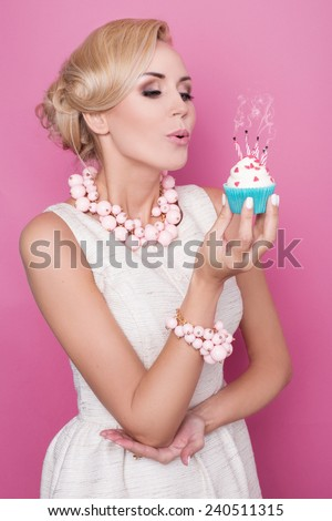 Elegant woman blowing out candles on birthday cake. Studio portrait over pink background - stock photo