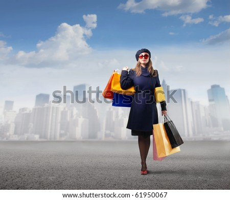 Elegant woman carrying some shopping bags with cityscape on the background - stock photo