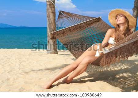 Elegant woman in a bikini reclining in a hammock strung between palm trees on the beach at a tropical resort - stock photo