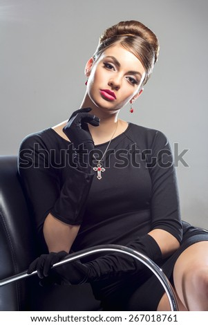 Elegant woman in a black dress and long gloves sitting in a black contemporary armchair on a grey background - stock photo