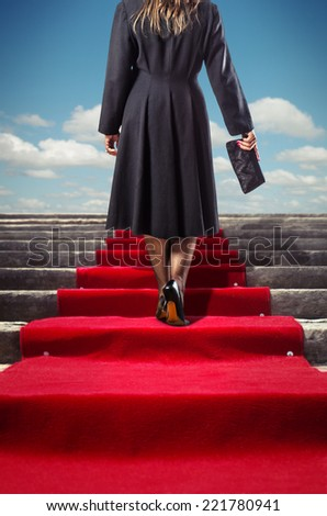 Elegant woman in black coat climbing a red carpet stairway - stock photo