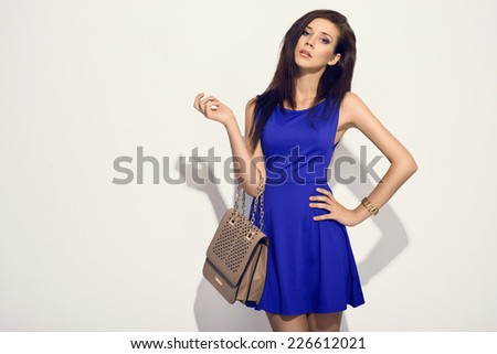 elegant woman in blue dress holding handbag posing in the studio  - stock photo