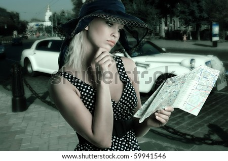 elegant woman in blue polka dot dress and hat looking at a tourist map - stock photo