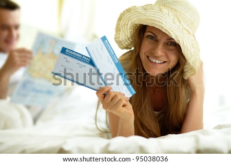 Elegant woman in hat holding flight tickets and looking at camera - stock photo