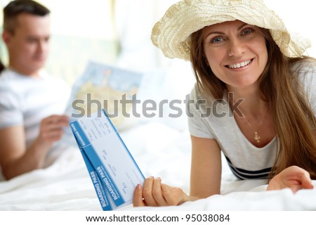 Elegant woman in hat holding flight tickets while looking at camera - stock photo