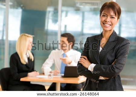 Elegant woman in smart suit looking at camera with smile at background of her busy colleagues